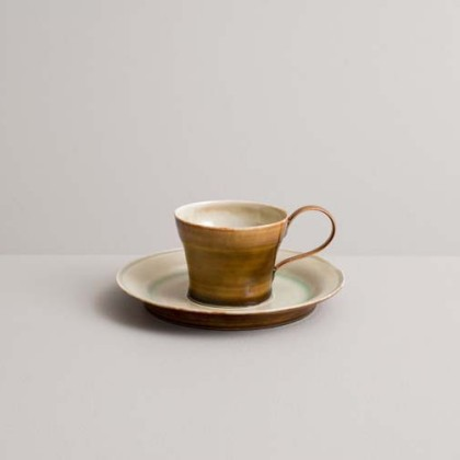 58. Espresso cup with saucer in  ivory-green and amber glazes  Wheel-thrown porcelain 7 x 14.5 cm